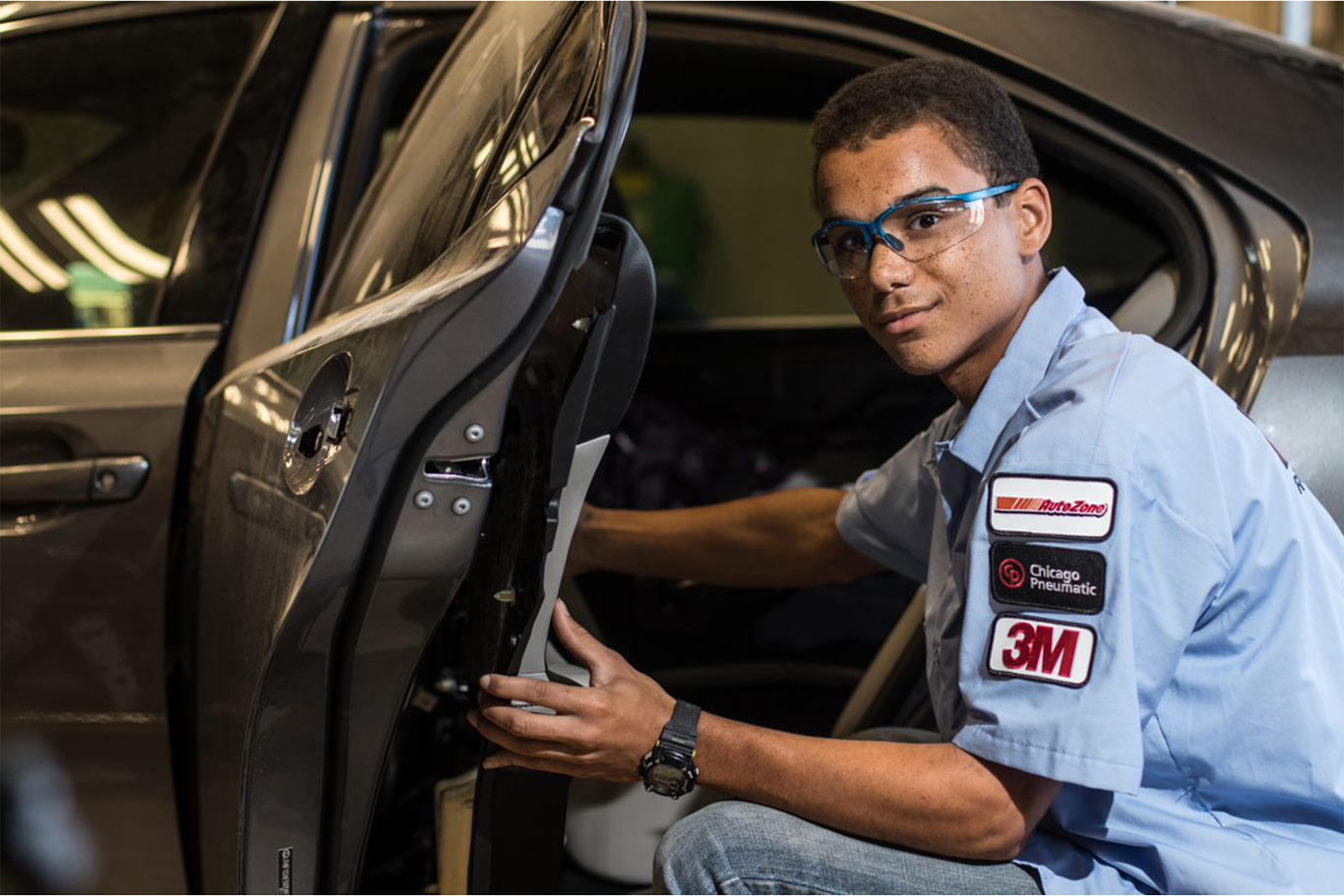 Man smiling with protective goggles on knealing down beside a car door