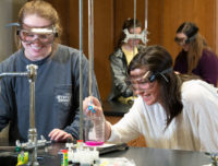 Girls in lab with goggles on smiling while doing an experiment