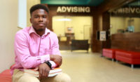 """Man sitting in hallway with books in front of a sign that reads """"ADVISING"""""""