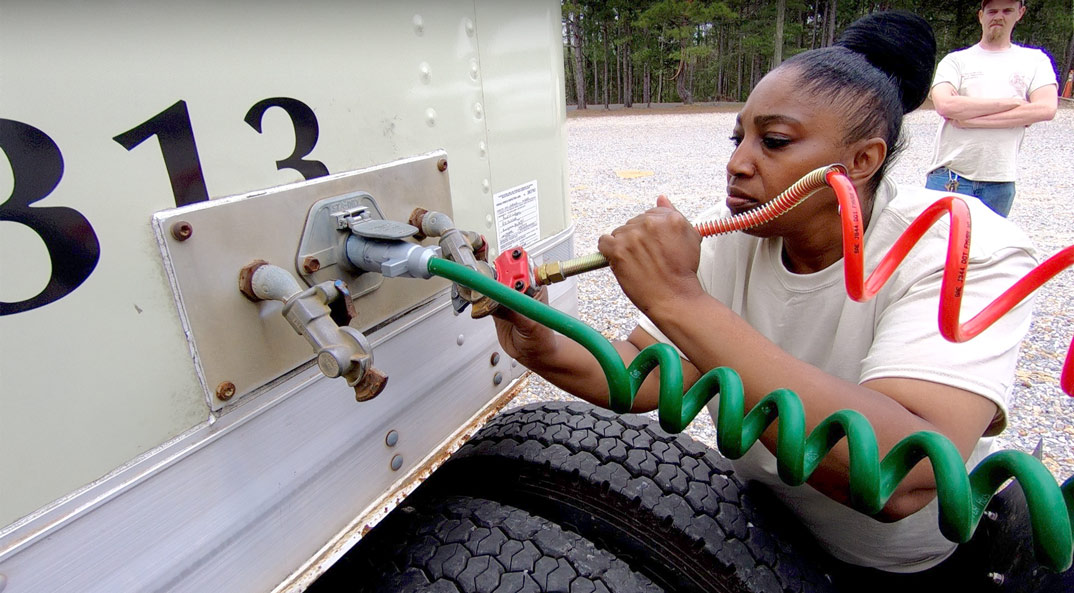 Reid State Trucking female connecting a coil to the truck