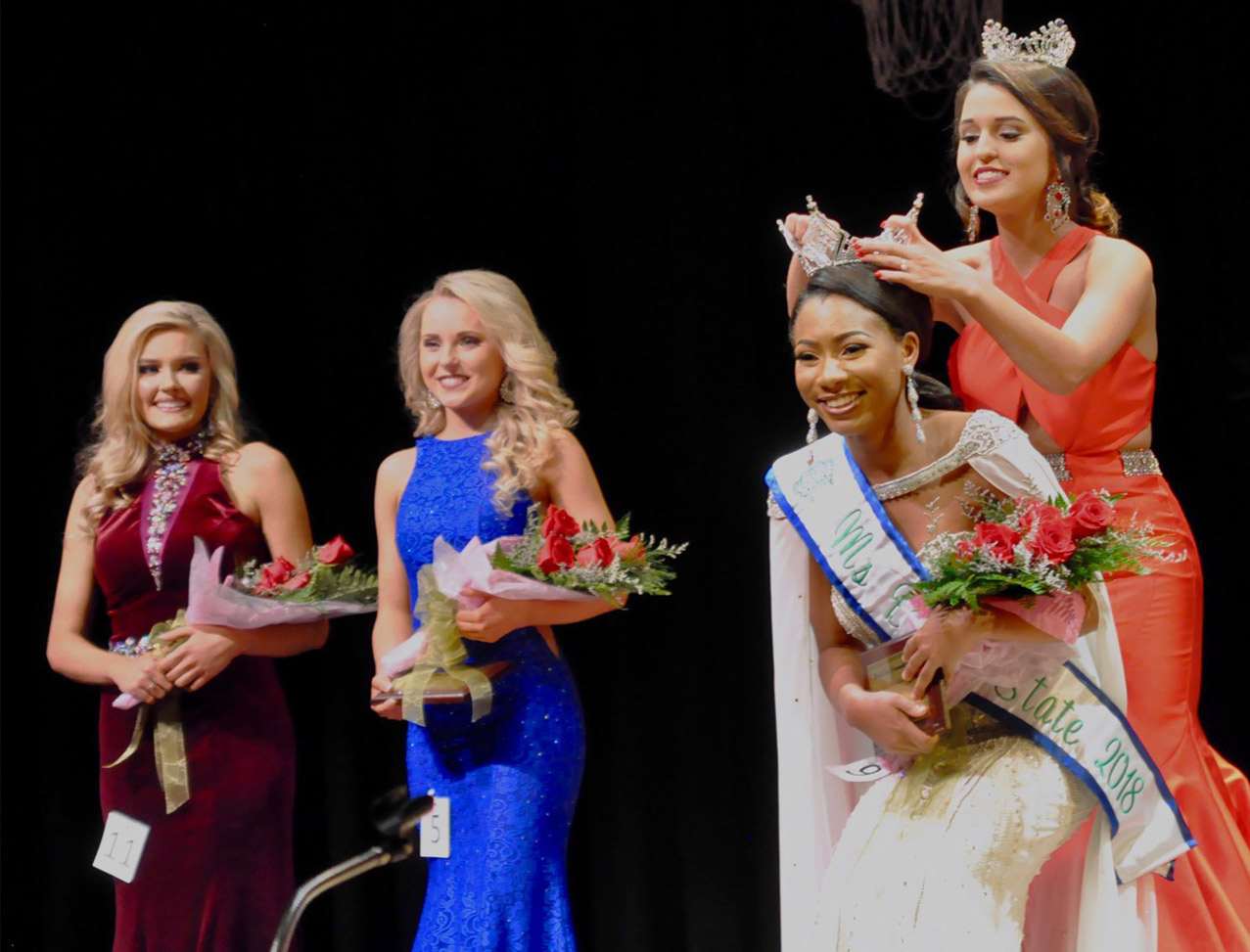 Former pageant queen crowning the current Ms. Bevill State 2018 with runner-ups smiling in the background