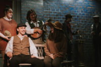 Theatre Group in Costume sitting on a bench onstage