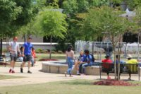 Multiple students moving around campus near the fountain