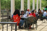 Three students sitting outside at a table conversing