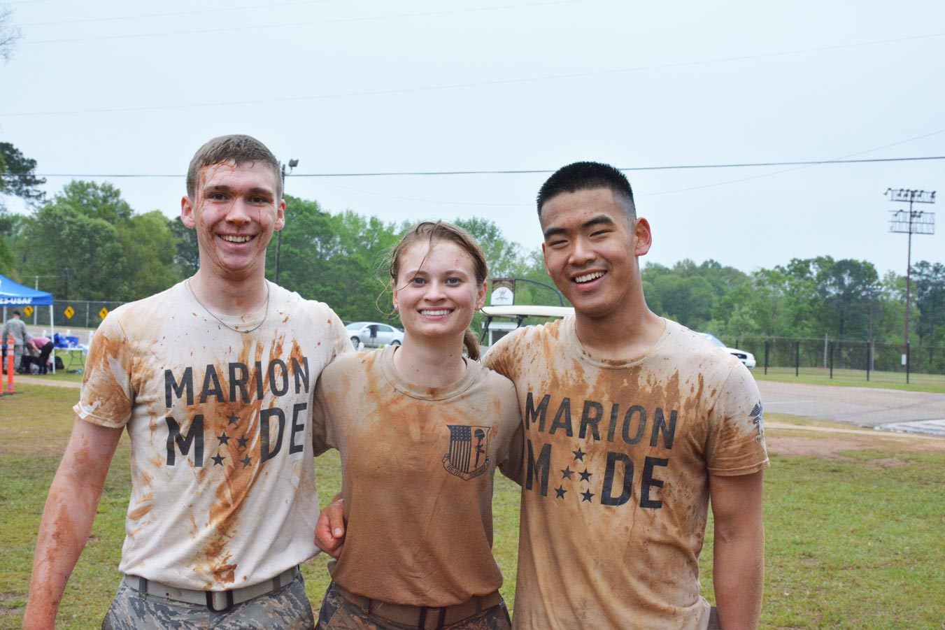Marion Made students covered in mud smiling for a picture