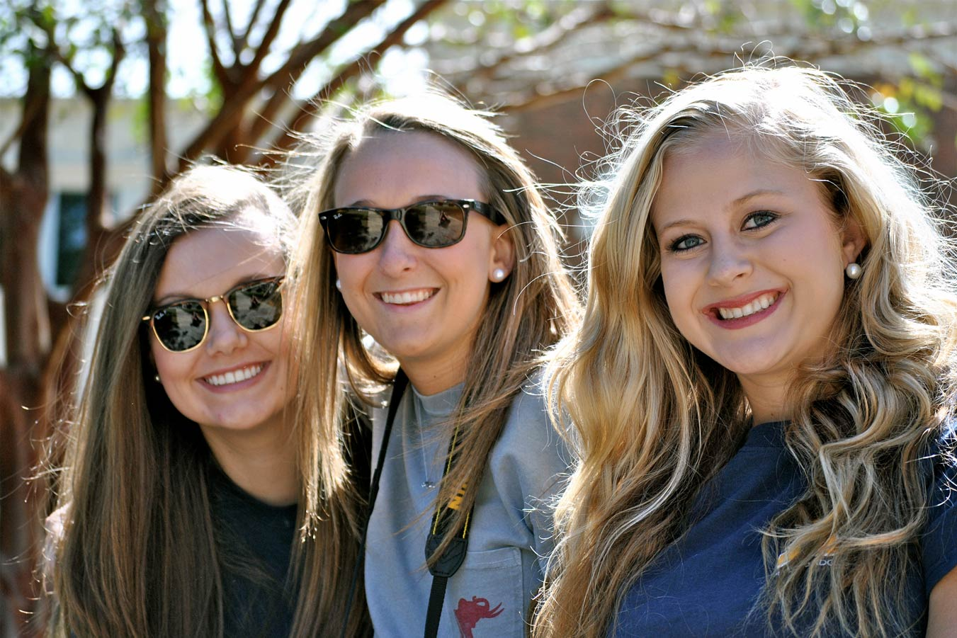 Close-up of three females smiling for a picture outdoors
