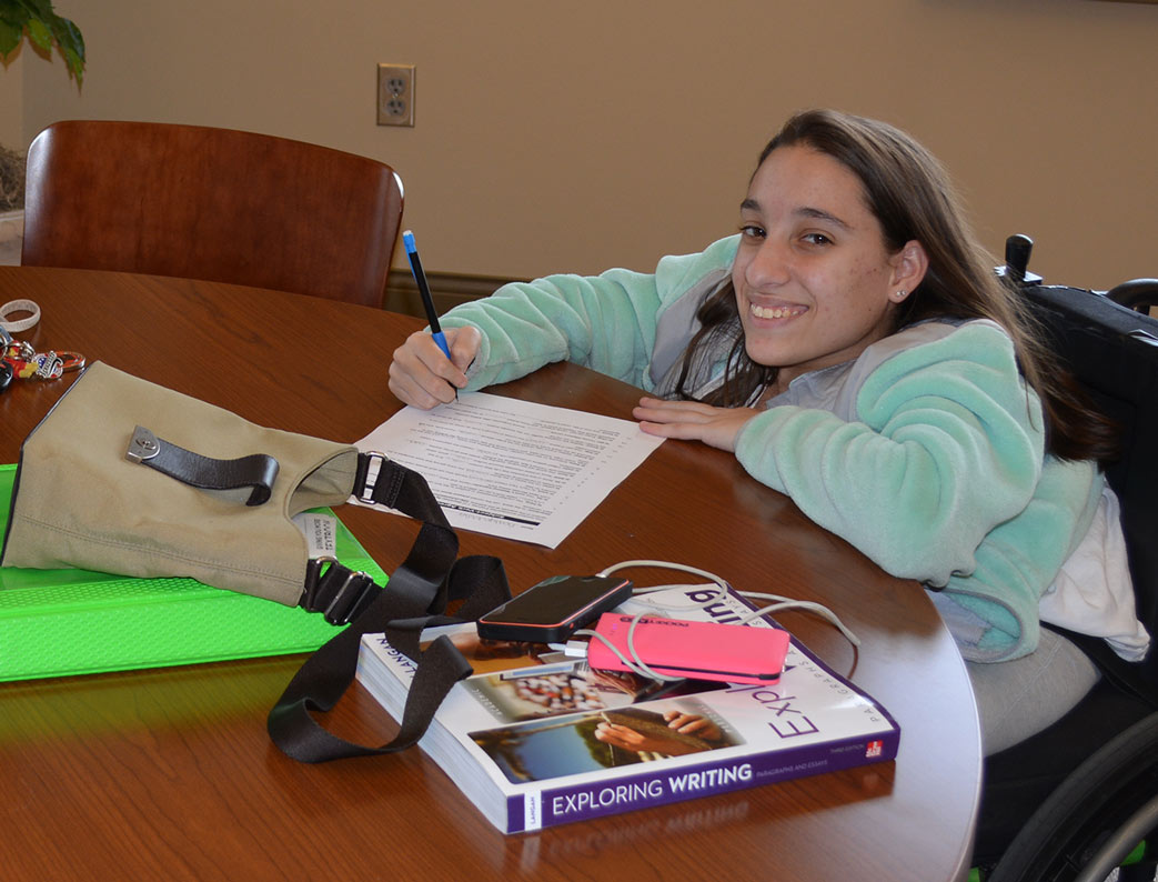 Female student in a wheelchair smiling at the camera while she studies
