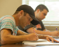 Male student writing in spiral notebook with a pencil