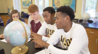 Three male and one female student observing a globe