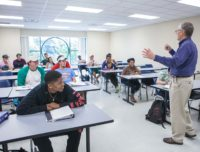 Teacher motioning to students in classroom